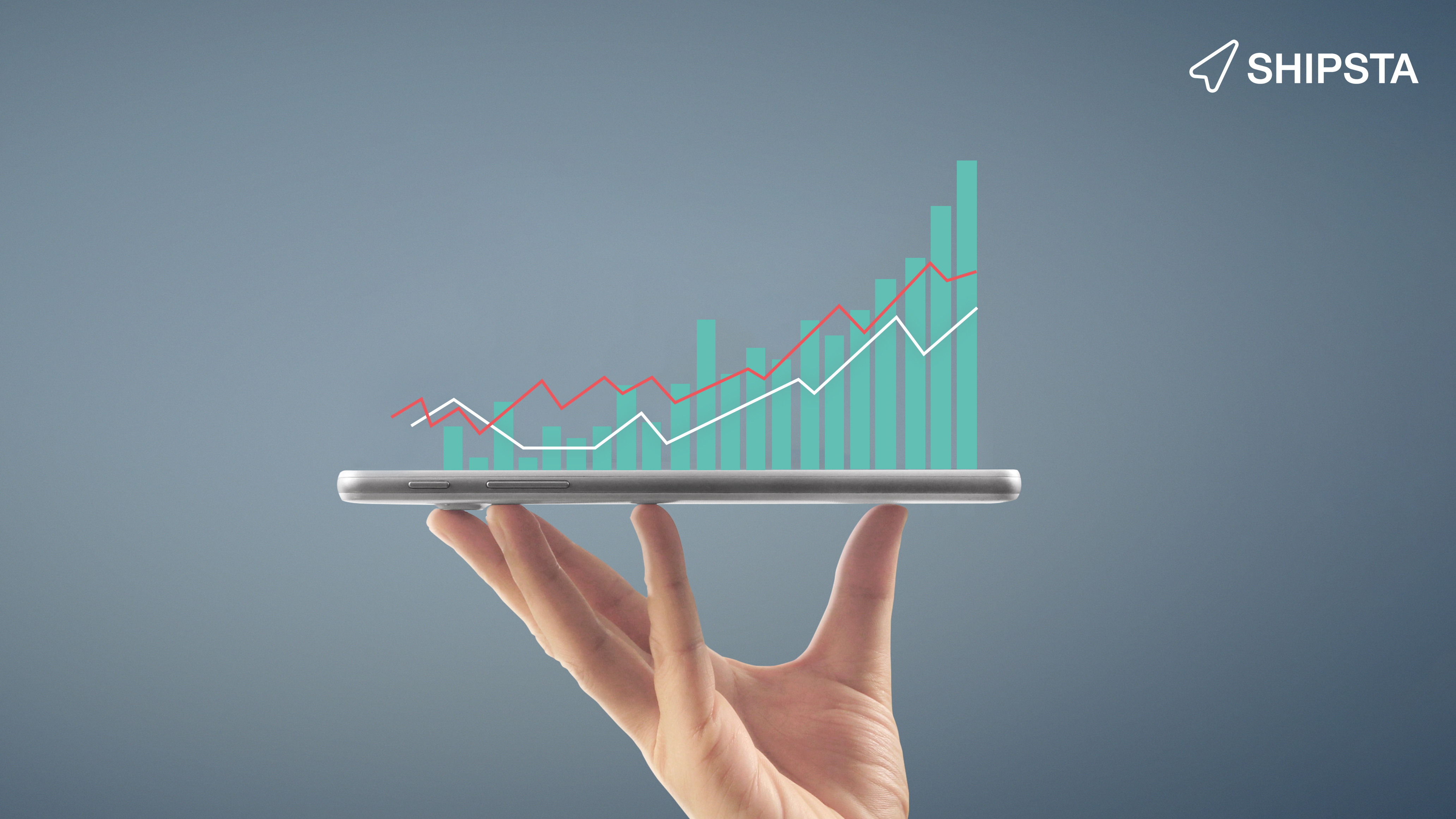 Hand holding a tablet with a graph on it.